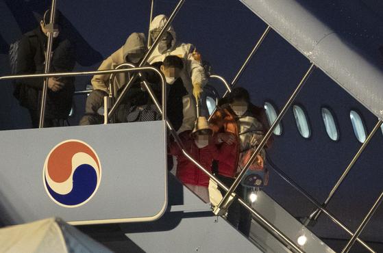 중국 후베이성 우한에 거주 중인 교민들이 12일 김포공항을 통해 귀국해 전세기에서 내리고 있다. [연합뉴스]