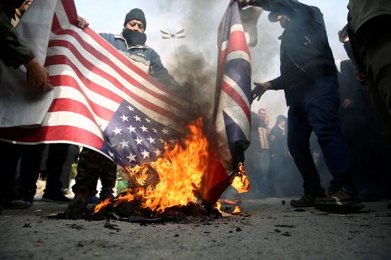 지난달 3일 이란 테헤란 시민들이 거셈 솔레이마니 이란혁명수비대 사령관 사망에 항의하며 미국과 영국 국기를 불태우고 있다. [사진=로이터]