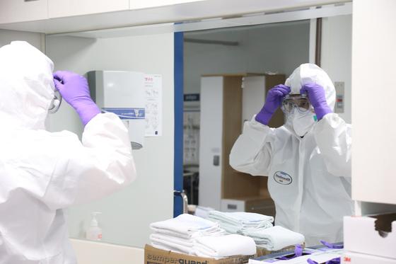 서울대병원 감염격리병동 의료진이 음압병동에 들어가기 위해 레벨D 방호복을 착용하고 있다. [중앙포토]