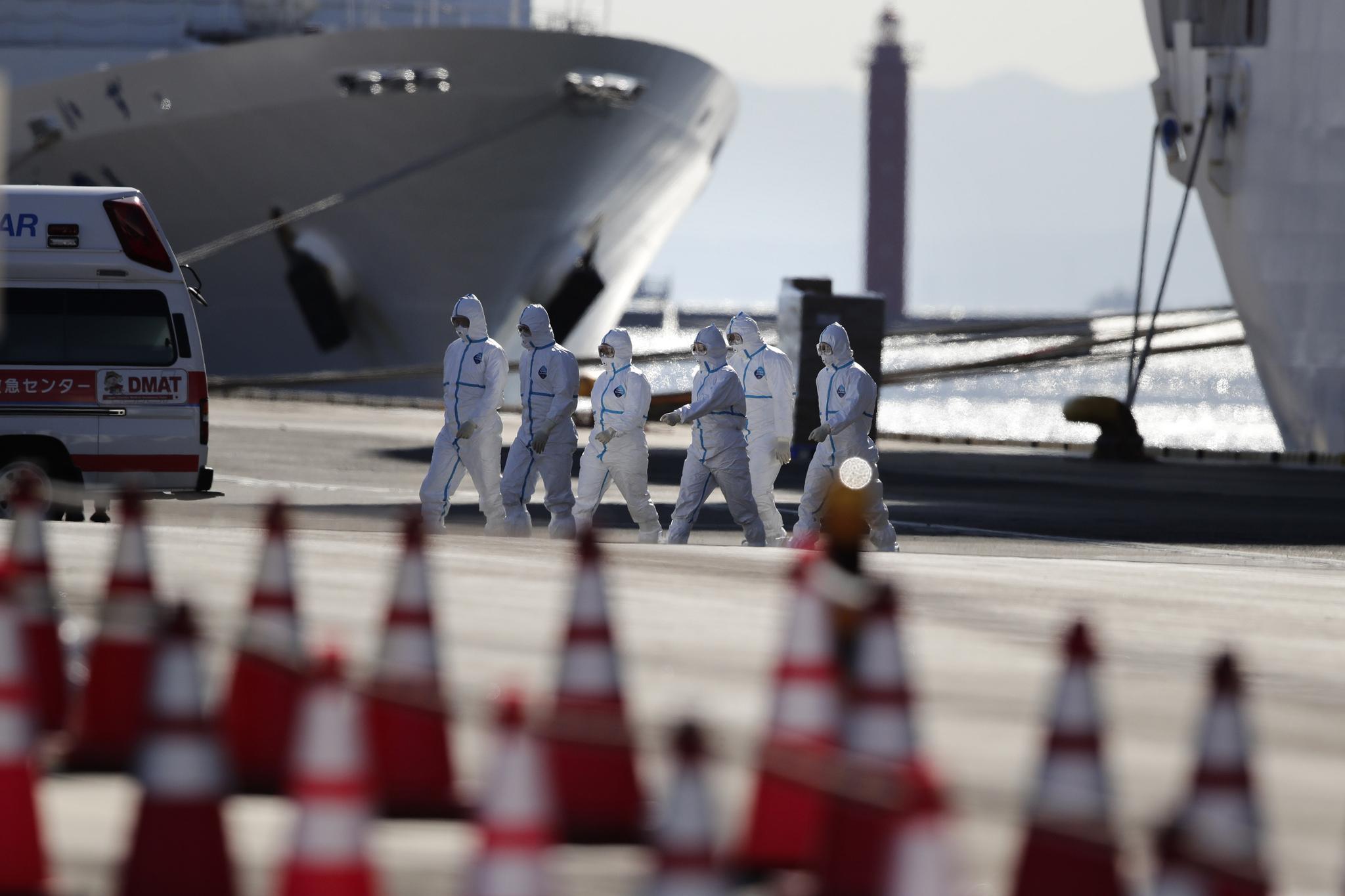 일본 요코하마항에 정박한 채 격리된 다이아몬드 프린세스 크루즈선 앞에서 보호복을 입은 의료진이 이동하고 있다. [AP=연합뉴스]