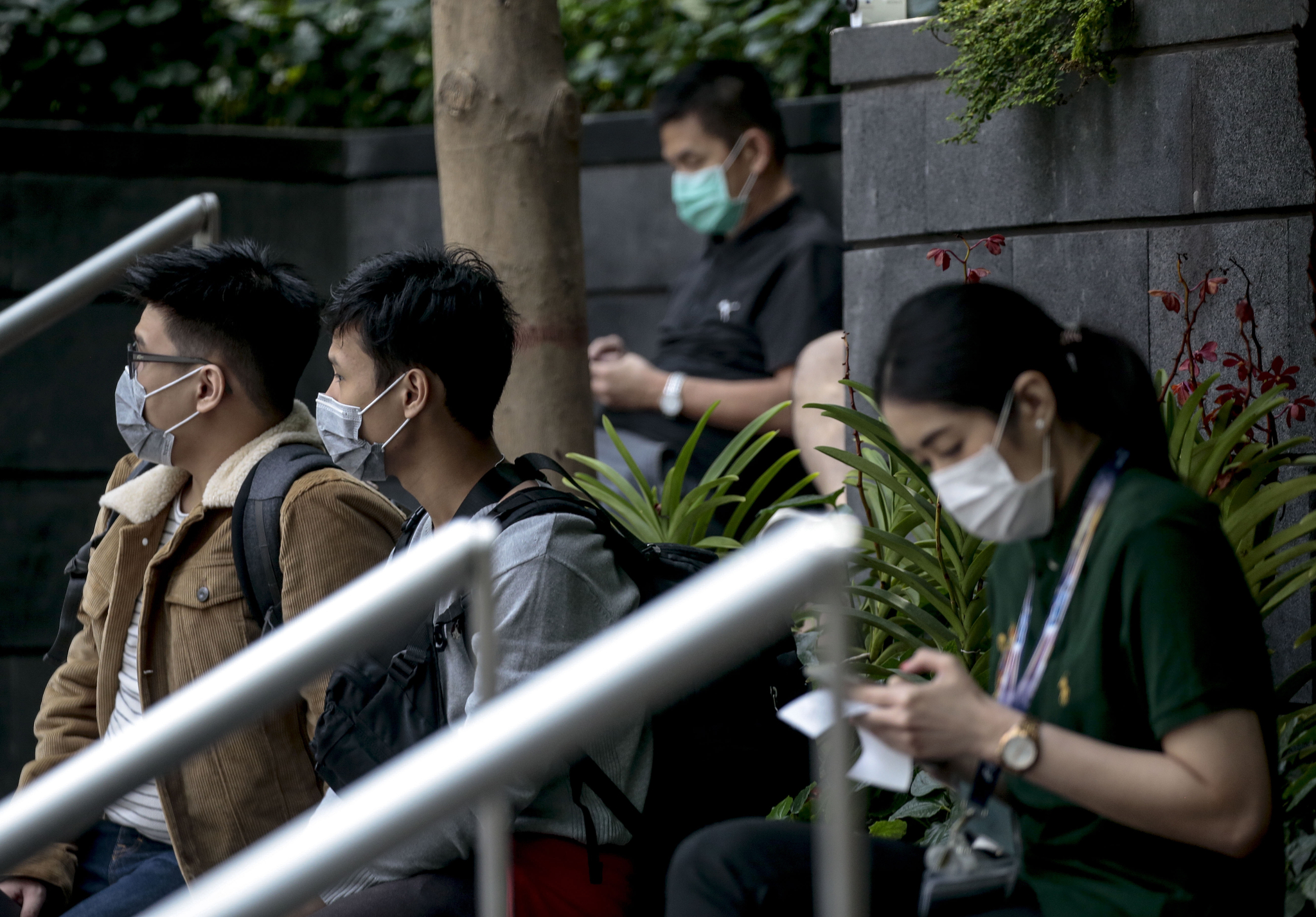 지난 13일 싱가포르 창이공항에 앉아있는 사람들이 모두 마스크를 쓰고 있다. [EPA=연합뉴스]