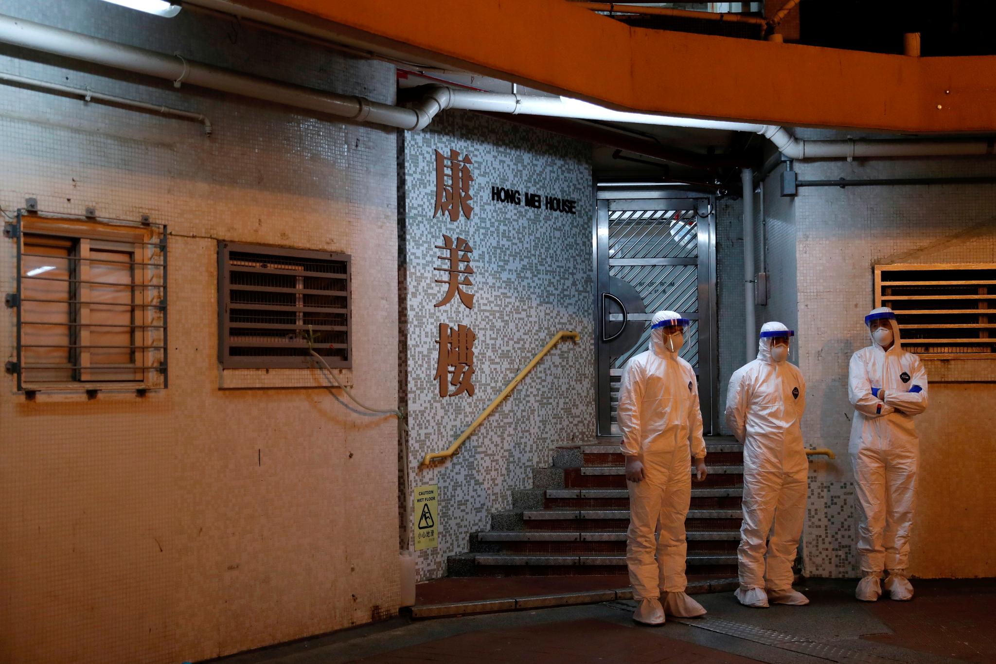 지난 11일 홍콩에서 방호복을 입은 역학조사관들이 건물 내 거주민들을 대피시키기 위해 준비하고 있다. [로이터=연합뉴스]