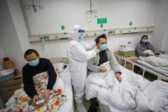 중국 후베이성 우한의 진인탄 병원에서 13일 의료진이 환자의 상태를 확인하고 있다. [EPA=연합뉴스]