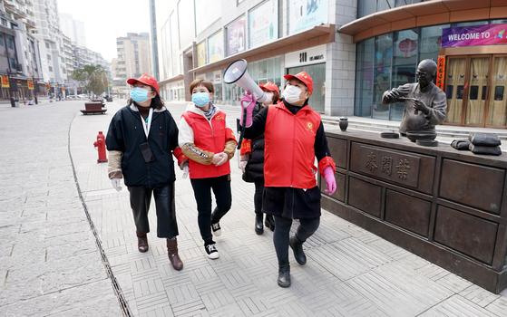 13일 중국 후베이성 우한 주민들이 신종 코로나바이러스 감염증 예방을 독려하며 순찰을 돌고 있다. [신화=연합뉴스]