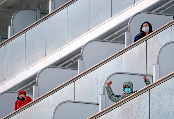 선내 신종 코로나바이러스 확진자 발생으로 일본 요코하마항에 정박 중인 크루즈선 다이아몬드 프린세스호 내 선실에 각기 격리된 승객들이 손을 흔들고 있다. [EPA=연합뉴스]