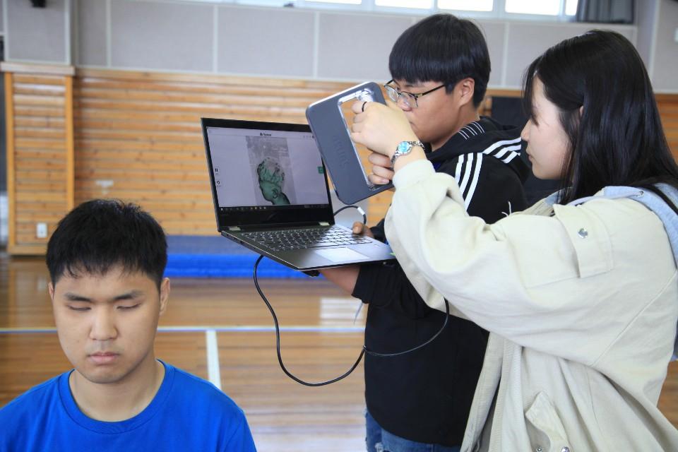 탈북 청소년 대안학교인 드림학교 고등학생들이 3D 프린팅 기술을 이용해 얼굴 모형을 완성하기 위해 전북맹아학교 졸업반 학생의 얼굴을 스캔하고 있다. [사진 전북맹아학교]