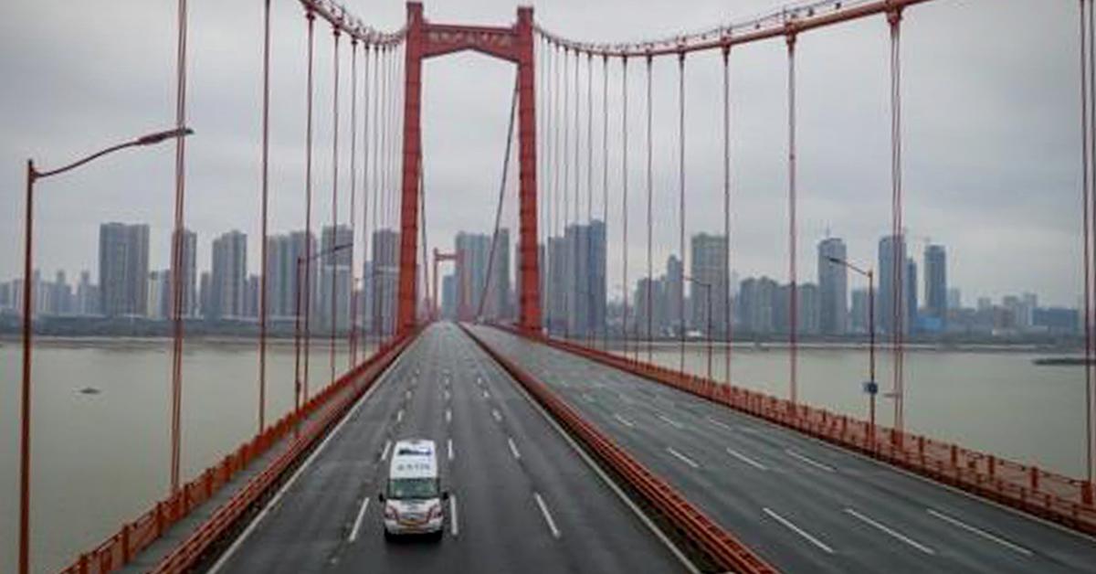 신종 코로나바이러스 감염증 발원지인 중국 후베이성 우한의 텅 빈 다리 위를 구급차 한 대가 달리고 있다. [EPA=연합뉴스]