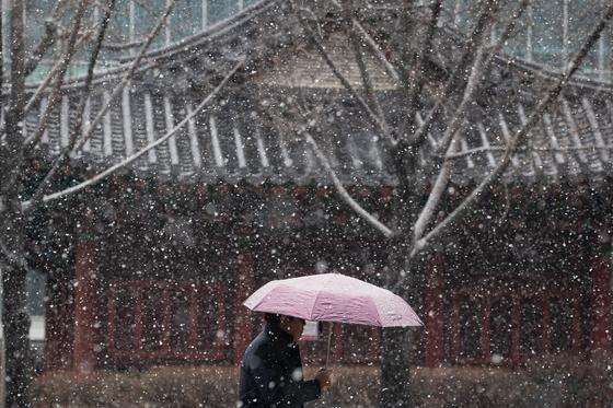눈이 내리는 16일 서울 종로구 인사동길에서 한 시민이 우산을 쓰고 지나가고 있다. [뉴스1]