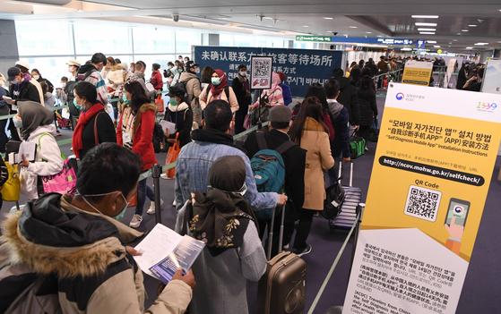 중국과 홍콩, 마카오에 대한 특별입국절차가 개시된 지난 13일 인천국제공항에서 홍콩 발 항공편 승객들이 '자가진단 앱' 설치를 위해 줄지어 서 있다. [연합뉴스]