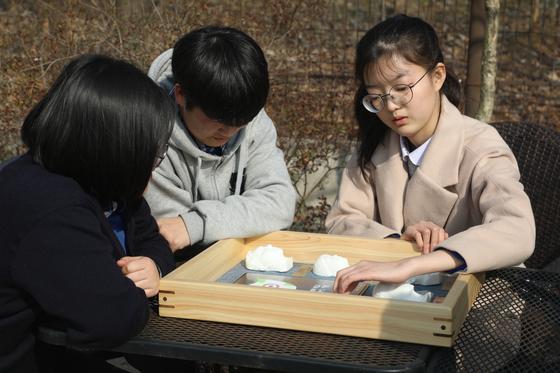 전북맹아학교 고등학교 3학년 학생들이 본인들의 얼굴을 본떠 만든 모형이 담긴 '3D 촉각 졸업 앨범'을 만져 보고 있다. [사진 전북맹아학교]