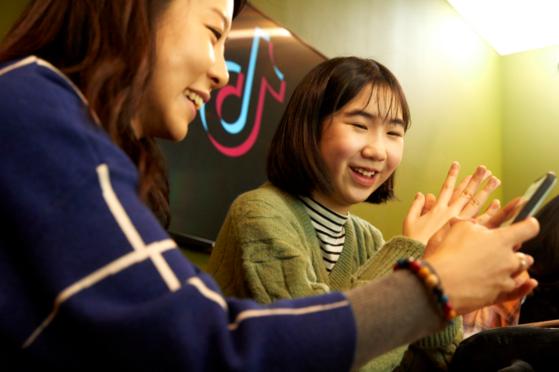 유다현 학생모델이 틱톡 관계자의 도움을 받아 앱 이용법을 익히고 있다.