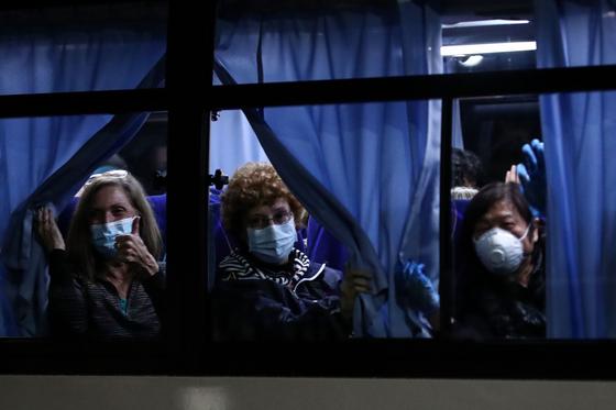 '다이아몬드 프린세스'호의 미국인 승객들이 17일 새벽 귀국 전세기를 타기 위해 버스를 타고 요코하마항을 떠나면서 창 밖을 보고 있다. [AFP=연합뉴스]