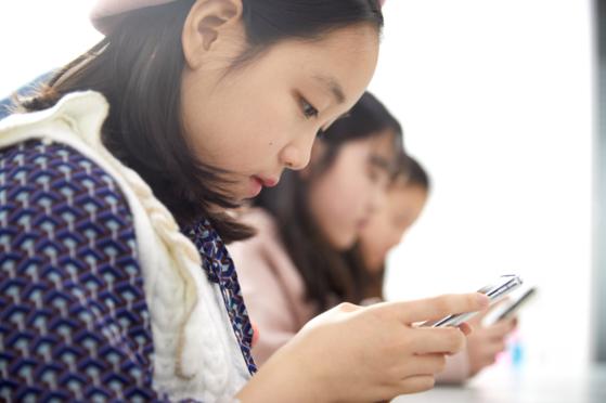 이은채 학생기자가 스마트폰으로 브이로그를 편집하고 있다.