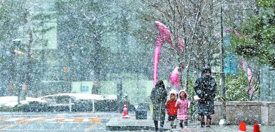 수도권과 제주도 산지에 대설주의보가 내려진 16일 서울 종로구 일대에서 시민들이 눈을 맞으며 걷고 있다. 기상청은 오늘(17일) 서울 아침기온이 영하 6도까지 떨어진다 고 예보했다. [뉴스1]
