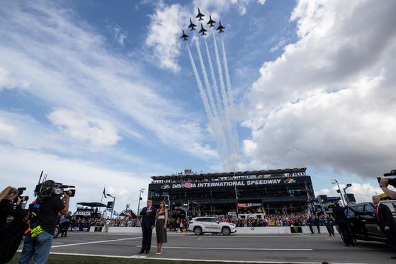 미 공군 특수비행단 선더볼트가 비행하는 가운데 트럼프 대통령과 부인 멜라니아 여사가 미국 국가를 부르고 있다.[AP=연합뉴스]