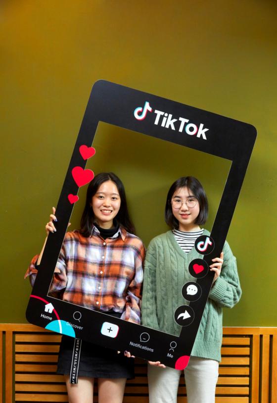 김나연(왼쪽) 학생기자와 유다현 학생모델이 틱톡 앱을 토대로 만든 설치물을 들고 카메라를 향해 웃어 보였다.