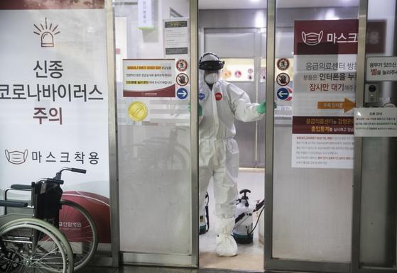국내 29번째 신종 코로나바이러스 감염증(코로나19) 환자가 다녀가 폐쇄된 고대안암병원 응급실에서 16일 한 보건소 관계자가 방역 작업을 위해 문을 닫고 있다. [연합뉴스]