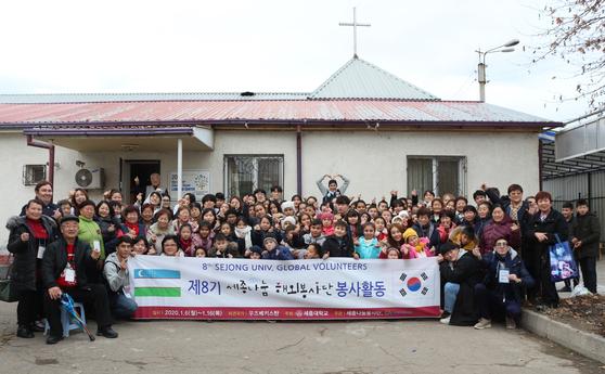 세종나눔봉사단 학생과 마을주민들이 교육 봉사 종료 후 이크센터 앞에서 기념촬영을 하고 있다.