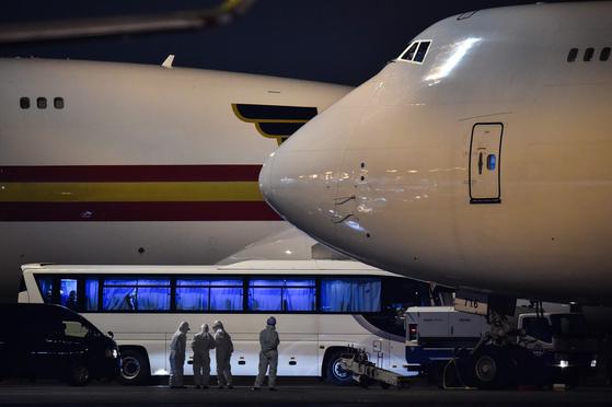 17일 밤 도쿄 하네다 공항 활주로에 요코하마 항에 2주간 격리됐던 다이아몬드 프린세스호 승객을 태운 버스가 보잉 747 전세기 옆에 서 있다. 미 국무부는 무증상을 보인 328명 승객을 송환하려 15대 버스로 이동하던 중 14명이 신종 코로나바이러스에 감염됐다는 통보를 받았지만 전세기에 태워 그대로 송환했다.[AFP=연합뉴스]