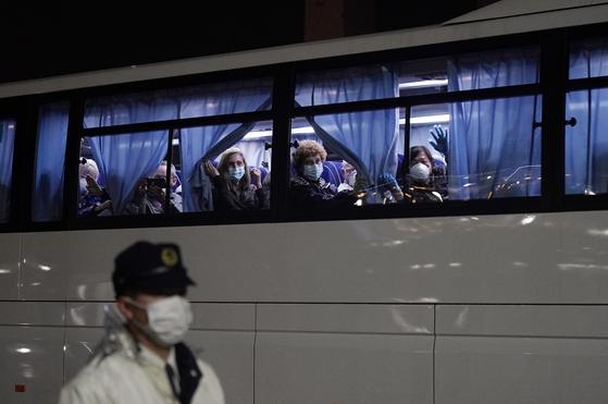 17일 신종 코로나바이러스 감염증(코로나19) 확산 방지를 위해 일본 요코하마항에 격리 정박 중이던 크루즈선 '다이아몬드 프린세스호'에 타고 있던 미국인들이 미국으로 돌아가기 위한 버스에 탑승해 손을 흔들고 있다. [EPA=연합뉴스]