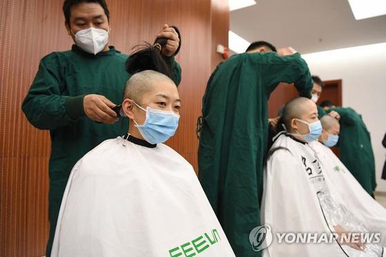 지난 15일 간쑤성 한 병원의 여성 의료진들이 삭발하고 있다. [신화=연합뉴스]