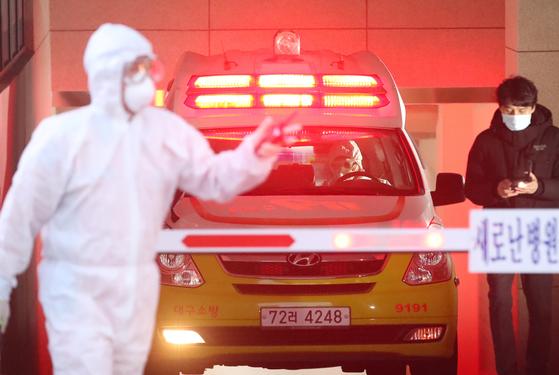 18일 신종 코로나바이러스 감염증(코로나19) 국내 31번째 확진자가 입원했던 것으로 알려진 대구 수성구 범어동 새로난한방병원에서 질병관리본부와 119구급대원들이 구급차를 이용해 해당 병원에 남은 환자들을 타 병원으로 이송하고 있다. [뉴스1]