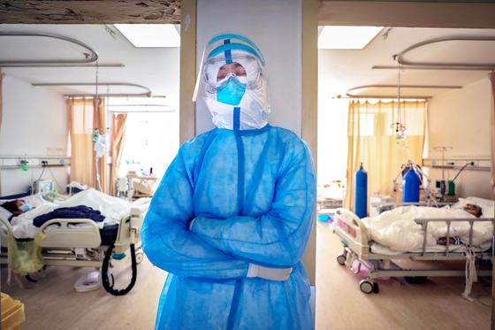지난 16일 중국 우한시의 한 병원에서 의료진이 벽에 기댄 채로 잠시 졸고 있다. [AP=연합뉴스]