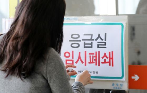 20일 오후 경기도 수원시 아주대병원에서 관계자들이 신종코로나감염증(코로나19) 의심환자가 내원한 응급실 폐쇄를 알리는 안내문을 부착하고 있다. [뉴스1]
