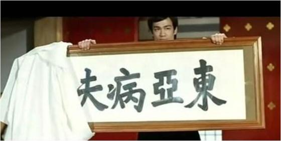 영화 '정무문'에서 배우 브루스 리가 '아시아의 병자'라고 쓰여진 현판을 들고 있다. 그는 이 현판을 부순다. [inmediahk.net]