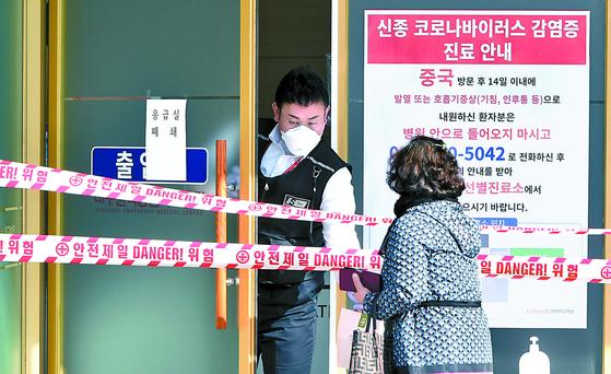 음압병상에 입원 중인 환자 가운데 신종 코로나바이러스 감염증(코로나19) 양성 반응이 나와 폐쇄된 대구 경북대병원 응급실 입구에서 19일 보안 요원과 방문객이 이야기를 나누고 있다. 이날 하루 만에 22명의 환자가 새로 나와 국내 코로나19 확진자는 53명으로 늘었다. [뉴시스]