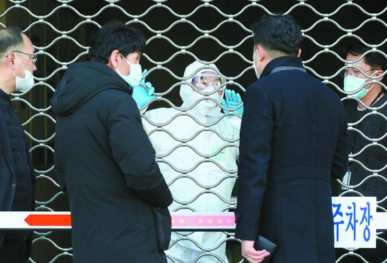 18일 오후 대구 새로난한방병원 주차장 셔터 앞에서 방호복을 입은 질병관리본부 관계자와 경찰관이 환자 이송에 대한 이야기를 나누고 있다. [뉴스1]