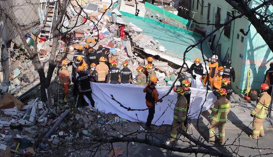 21일 부산시 연제구에서 발생한 2층짜리 단독주택 붕괴사고 현장에서 소방대원들이 5명의 매몰자 중 마지막 매몰자를 구조하고 있다. 송봉근 기자