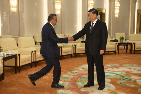 테드로스 아드하놈 게브레예수스(왼쪽) 세계보건기구(WHO) 사무총장이 지난달 28일 중국 베이징을 방문, 시진핑 중국 국가주석과 만나 웃으며 손을 맞잡고 있다. [AP=연합뉴스]
