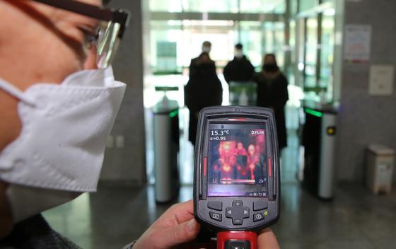 지난 19일 부산 남구 동명대 기숙사에 발열감지기가 설치돼 직원이 출입하는 학생들의 체온을 체크하고 있다. 부산에서는 22일 오전 현재 3명의 코로나19 확진자가 발생했다. 송봉근 기자