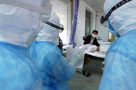 지난 2003년 5월 13일 중국 베이징의 한 병원에서 의료진이 사스 의심환자와 멀리 떨어져 역학조사 질문을 하고 있다. 당시 중국 본토에서만 349명의 사망자가 발생, 중국은 국제사회로부터 부실한 보건시스템에 대한 비판을 받았다. [로이터=연합뉴스]