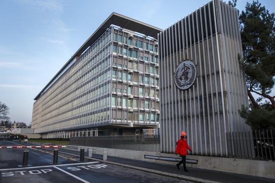 지난달 22일 스위스 제네바에 있는 세계보건기구 WHO의 본부 앞을 한 여성이 지나가고 있다. [EPA=연합뉴스]