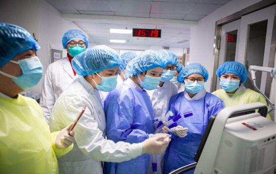 신종 코로나바이러스와 사투를 벌이는 중국의 의료진이 모니터를 보며 나타난 결과에 환호하고 있다. [중국 인민망 캡처]