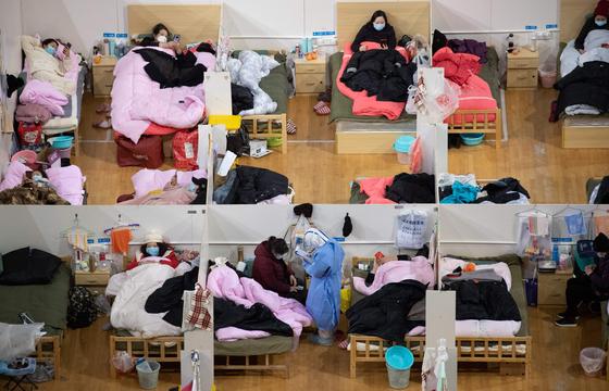 코로나 19의 발원지인 후베이성 우한의 체육관에 설치된 임시병원의 칸막이가 쳐진 공간에 경증 환자들이 쉬고 있는 모습이 보인다. [AFP=연합뉴스]