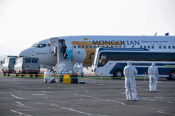 지난 1일 중국 우한에서 전세기를 타고 도착한 몽골인들이 울란바토르 공항에 내리고 있다. [AFP=연합뉴스]