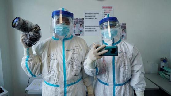 중국 신화사 기자들이 방호복을 입고 신종 코로나바이러스와 사투를 벌이는 의료 현장을 취재하고 있다. [중국 신화망 캡처]