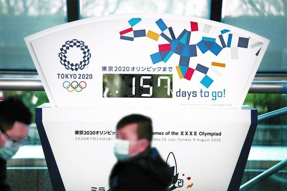코로나19 확산과 함께 도쿄올림픽 개최에 빨간불이 켜졌다. 올림픽 개막을 157일 앞둔 지난 18일 한 시민이 마스크를 쓰고 도쿄 시내 홍보 전광판 앞을 지나가고 있다. [AP=연합뉴스]