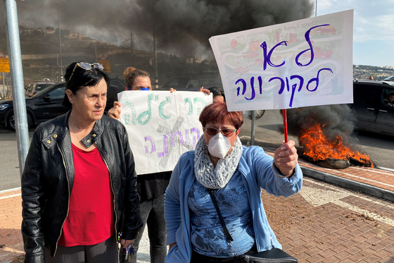 이스라엘 정부가 신종 코로나바이러스 감염증 전파를 우려해 한국인 관광객들을 요르단강 서안지구 내 유대인 정착촌인 하르 길로의 군사기지에 격리할 수 있다는 보도가 나오자 해당 주민들이 23일 '코로나 반대'라고 쓰인 플래카드를 들고 반대 시위를 벌이고 있다. [로이터=연합뉴스]