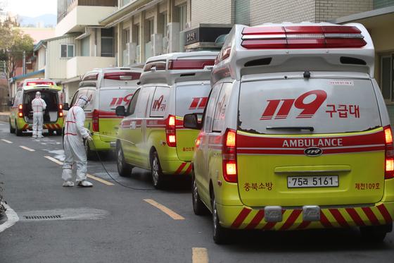 신종 코로나바이러스 감염증(코로나19)가 계속 확산하는 가운데 24일 오후 코로나19 지역거점병원인 계명대학교 대구동산병원으로 119구급차를 이용해 확진 환자가 도착하자 방역요원들이 구급차를 소독하고 있다. [뉴스1]
