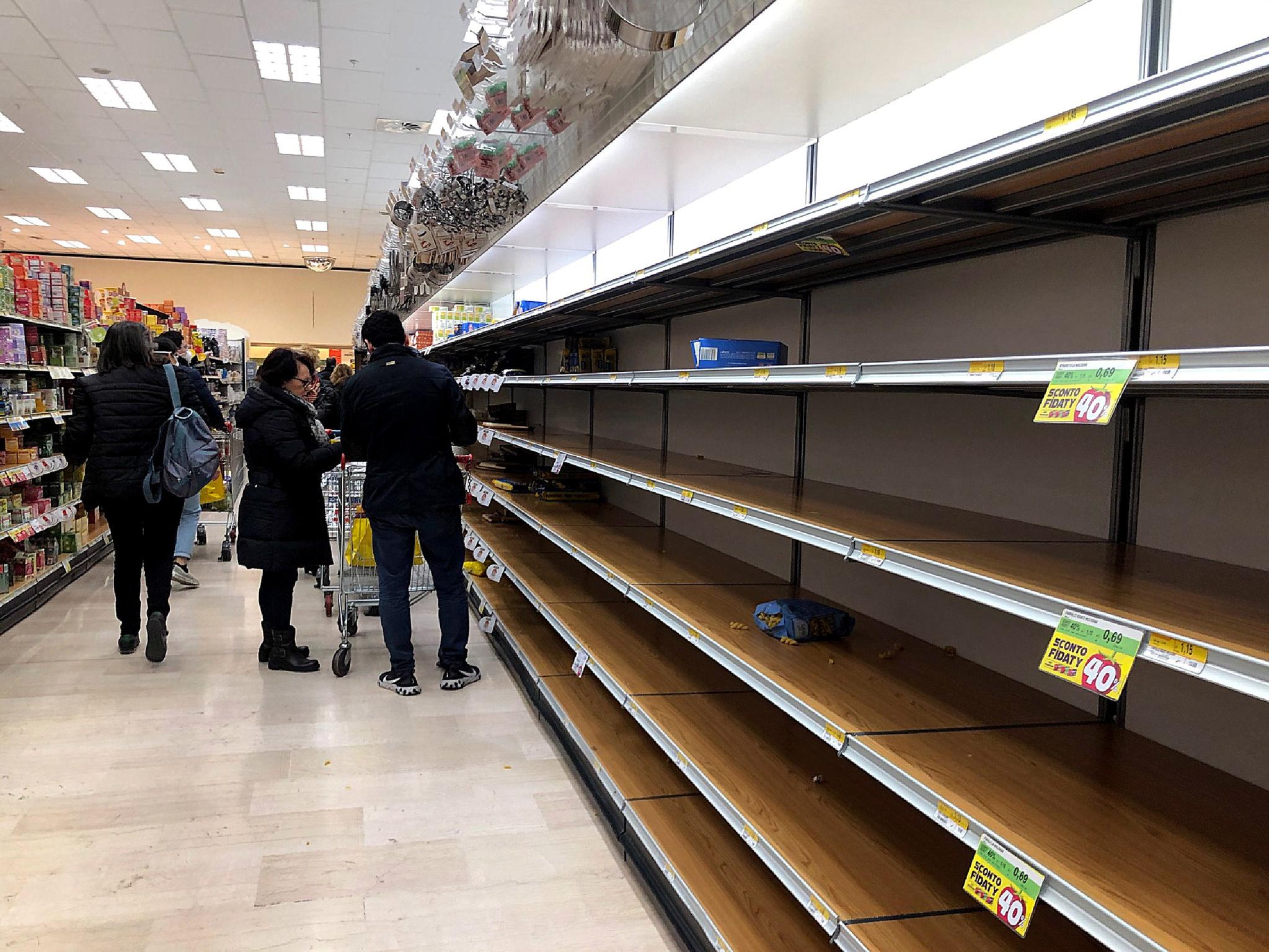 23일(현지시간) 코로나19로 인한 주민들의 생필품 사재기로 이탈리아 밀라노의 한 슈퍼마켓 진열대가 텅비어 있다. [EPA=연합뉴스]