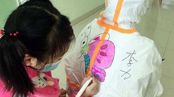중국의 한 어린이가 의료진의 방호복 뒤에 그림을 그리며 신종 코로나와의 사투 속에서도 천진난만한 동심을 표현하고 있다. [중국 신화망 캡처]