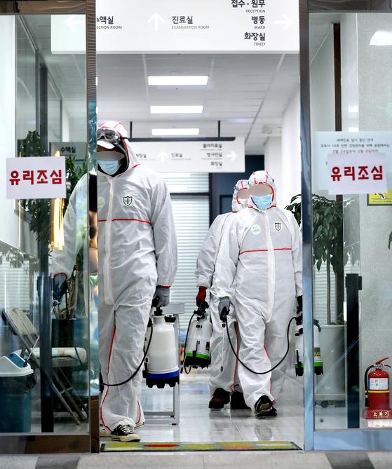 24일 오후 부산 연제구 아시아드요양병원과 같은 건물을 쓰는 1층 한 병원에서 병원 관계자가 방역하고 있다. 연합뉴스
