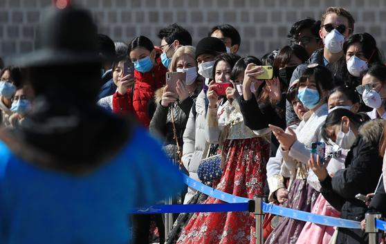 신종코로나바이러스감염증(코로나19)이 확산되는 가운데 23일 오후 서울 종로구 경복궁에서 마스크를 쓴 관광객이 수문장 교대 의식을 보고 있다. [연합뉴스]