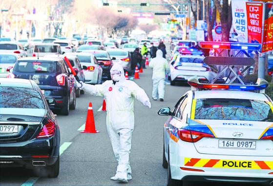 18일 오후 대구의 거리에서 방호복을 입은 경찰관이 주변 교통을 통제하는 등 환자 이송준비를 하고 있다. [뉴스1]