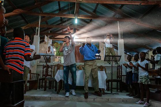 2010년 4월 후원 어린이들을 만나기 위해 아이티로 건너간 가수 션 씨가 현지 어린이센터에서 공연하는 모습.