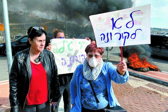 이스라엘 정부가 신종 코로나바이러스 감염증 전파를 우려해 한국인 관광객들을 요르단강 서안 지구 내 유대인 정착촌인 하르 길로의 군사기지에 격리할 수 있다는 보도가 나오자 해당 주민들이 23일 '코로나 반대'라고 쓰인 플래카드를 들고 반대 시위를 벌이고 있다. [로이터=연합뉴스]
